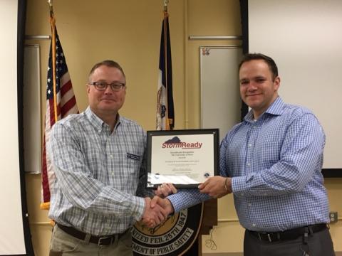 UI Emergency Management Coordinator Floyd Johnson accepts StormReady designation.