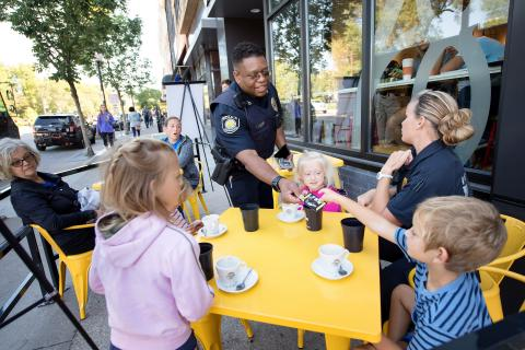 University of Iowa Police Officer Alton Poole shakes hands with members of the community during an outreach event downtown Iowa City.