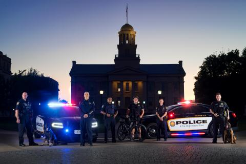 University of Iowa Police pose in front of the Old Capitol with squad cars at night.