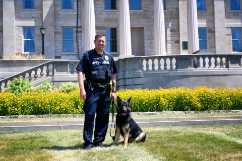 Officer Mohling and K9 Brad pose in front of the Old Capitol.