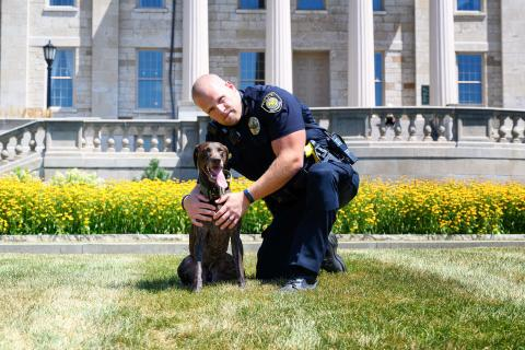 Officer Monter and K9 Hogan pose for a photo outside the Old Capitol.